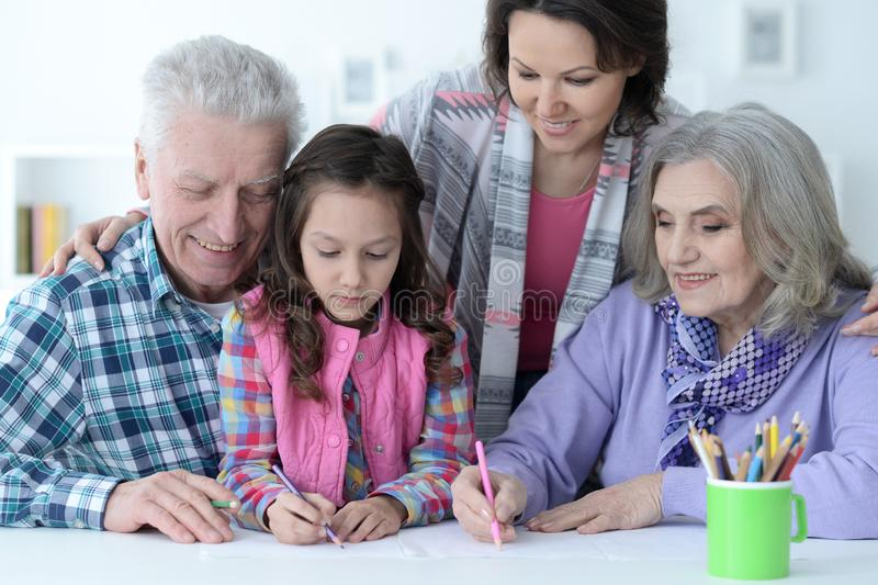 Big family with cute little girl doing homework stock photo