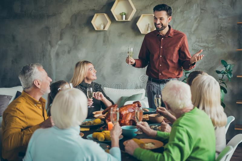 Big family happy thanksgiving celebration small little kids retired relatives mature parents sit table listen man toast stock images
