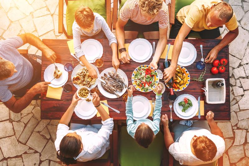 Big family have a dinner with fresh cooked meal on open garden terrace stock photography