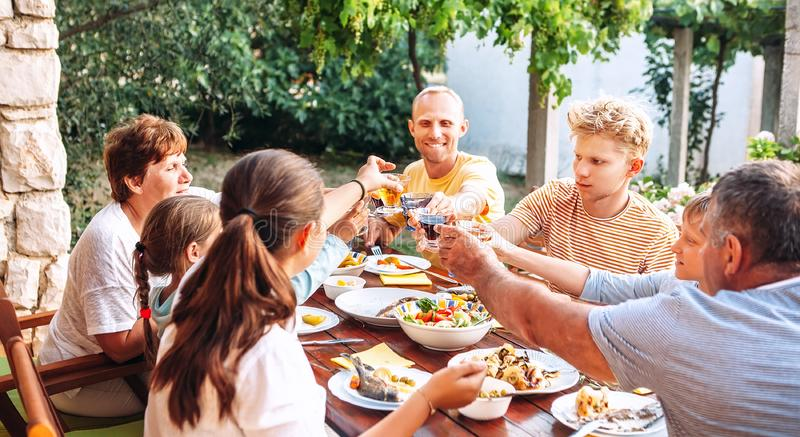 Big family have a dinner on garden terrace stock photography