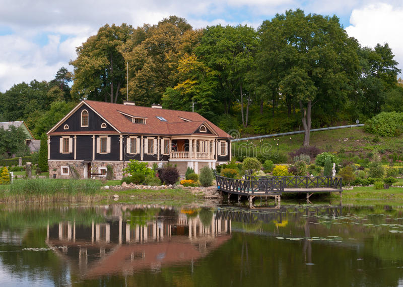 Big family house in front of the lake in the forest stock for Big family house