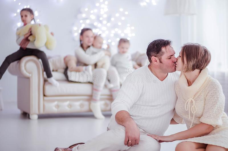 Big family in a New Year s interior. Husband and wife are looking at each other and kissing stock images