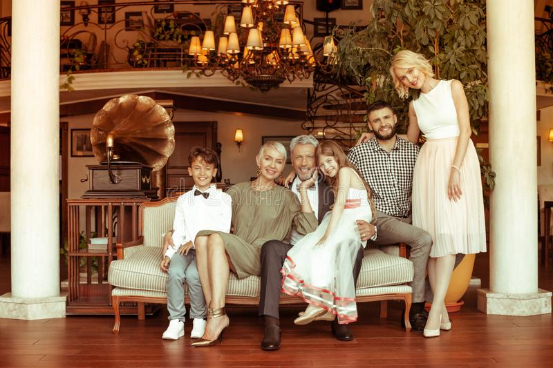 Big family siting on sofa while spending weekend together stock image