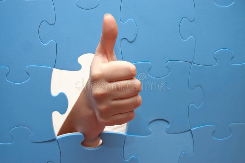 Big finger of a hand and puzzle stock photography