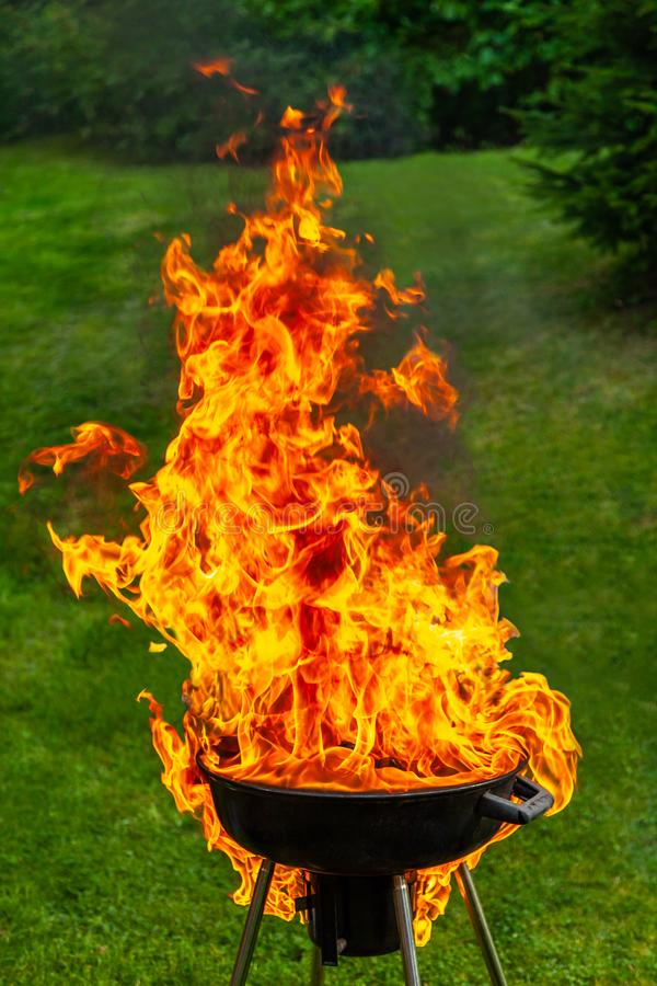 A big fire flashover a black grill outdoors. A big fire flashover a black grill outdoors when having a barbeque stock images