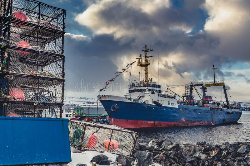 The big fishing ship at a pier. The big blue fishing ship at a pier with cages stock photo