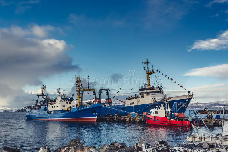 The big fishing ships at a pier. The big blue fishing ships at a pier with cages stock photo