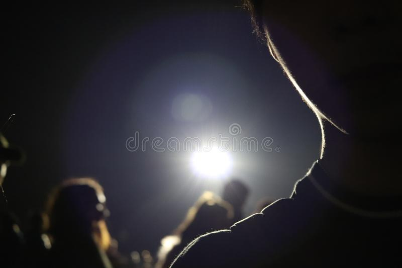 Big flash light on the dark night, having a man as a foreground stock image