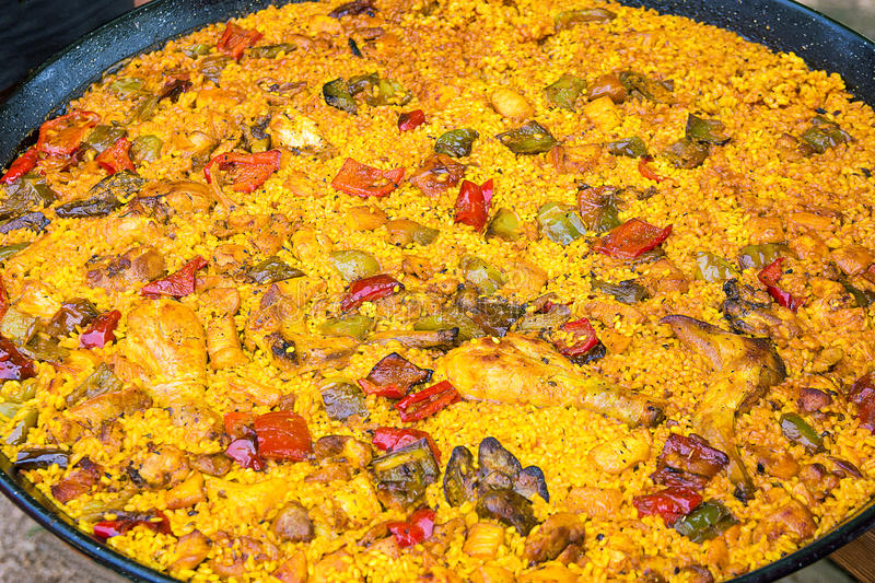 Big flat frying pan with home cooked Spanish paella. Variety of meat chicken, rabbit, vegetables, rice, tomato sauce, spices royalty free stock photos