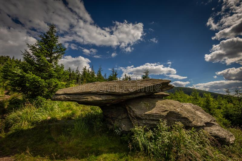 Big flat rock sitting on other on Obri Skaly with green grass, pine trees and dark blue cloudy sky under hill Serak in Jeseniky stock image