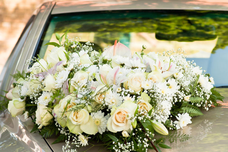 Big flower bouquet on bonnet. Big white flower bouquet on car bonnet. Horizontal shot stock image