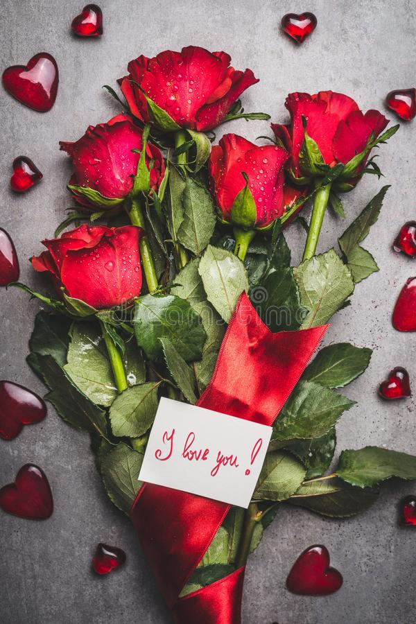 Big flowers bunch with red roses , ribbon , i love you lettering card and hearts on gray background stock photography