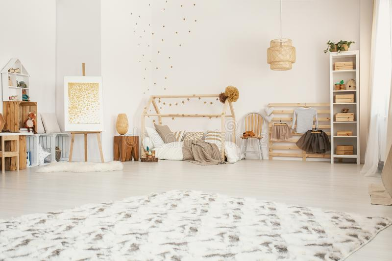 Big fluffy carpet placed on the floor in white Scandinavian style kid room interior with wooden furniture and home-shape bed stock photography