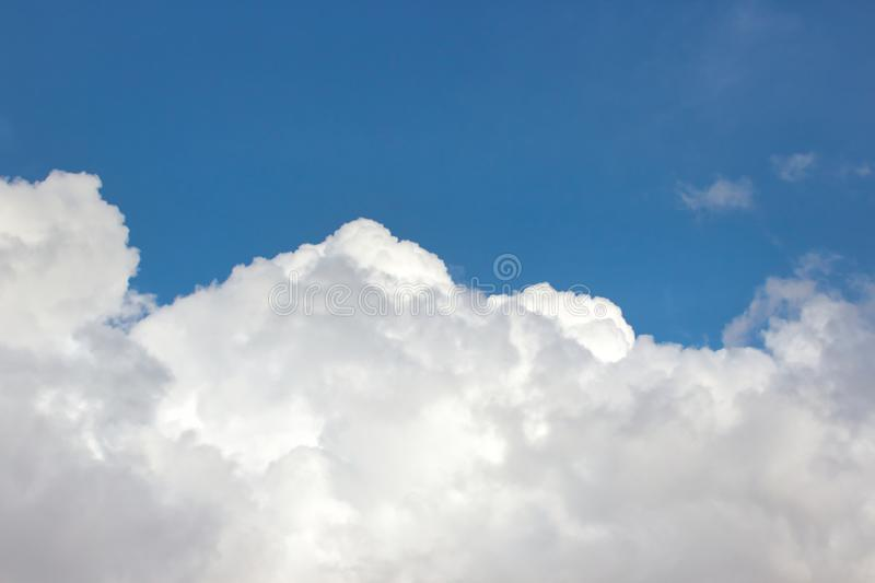 Big fluffy white clouds against a bright clear blue sky background royalty free stock image