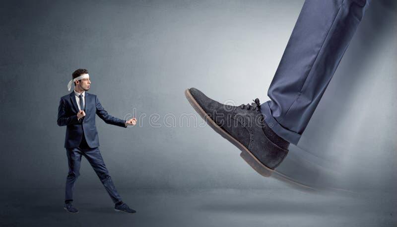Big foot treading small karate man stock photo