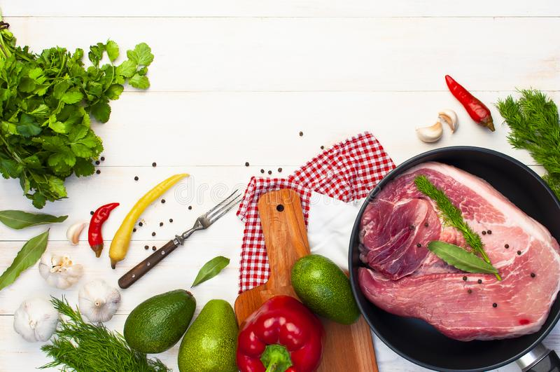 Big fresh piece of meat in the pan with ingredients for cooking pepper garlic avocado dill parsley on white wooden. Background top view. Raw steak from pork or royalty free stock photo