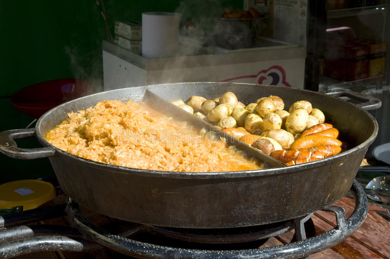 The big frying pan with hot meal. Rural meal. The big frying pan with hot meal stock photos