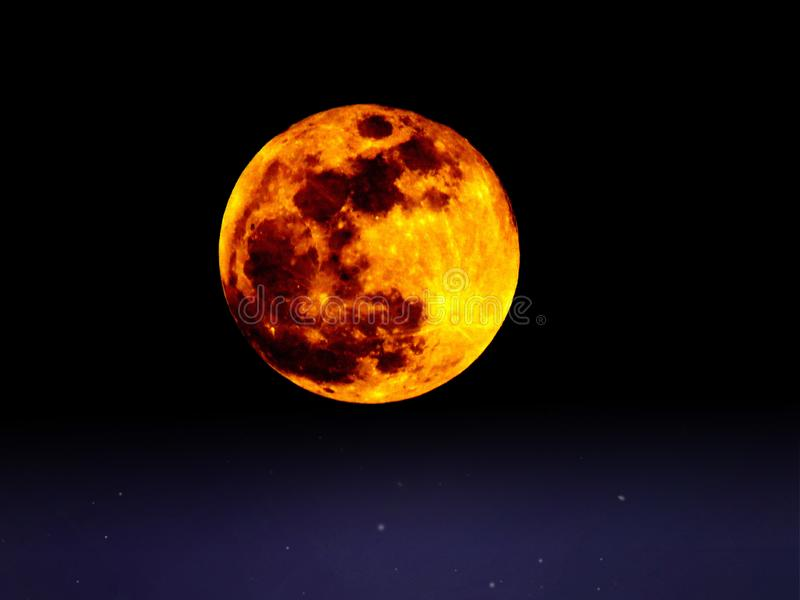 Big full colourful yellow red moon in dark blue sky and  some stars. Big full colourful yellow red moon in dark navy  blue sky and  some stars. Moon, sky royalty free stock image