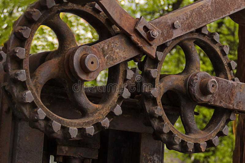 Big gear old mechanism engine group of shafts background industrial grunge street sawmill texture metal rusty close-up stock photography