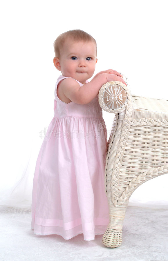 Big Girl Now. Baby girl learning to stand beside wicker bench royalty free stock photo