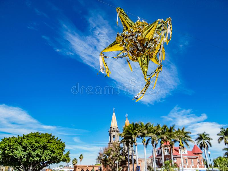 Mexican piñata against a blue sky, with a church and palmtrees in the background royalty free stock photos