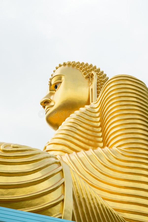 Big golden Buddha statue in wheel-turning pose. Big golden Buddha statue in sitting pose on the top of a building with cloudy white sky on background royalty free stock photography