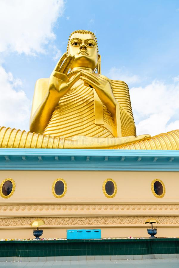 Big golden Buddha statue in wheel-turning pose. On the top of a building with blue sky on background stock image