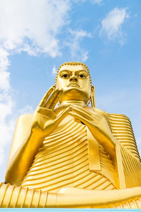 Big golden Buddha statue in wheel-turning pose. On the top of a building with blue sky on background royalty free stock photos