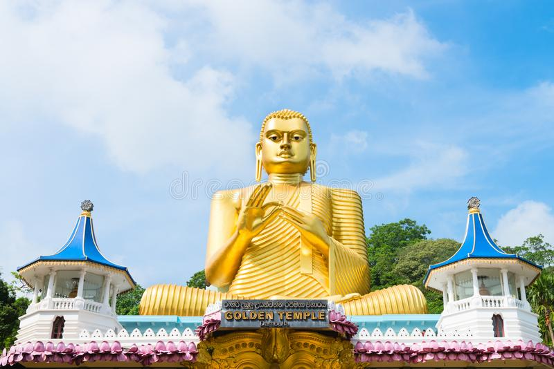 Big golden Buddha statue in wheel-turning pose in Dambulla Golden temple. Big golden Buddha statue in wheel-turning pose on the top of Golden cave temple in royalty free stock image
