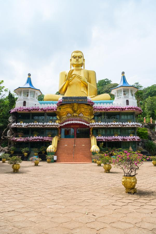 Big golden Buddha statue in wheel-turning pose in Dambulla Golden temple. Big golden Buddha statue in wheel-turning pose on the top of Golden cave temple in stock image