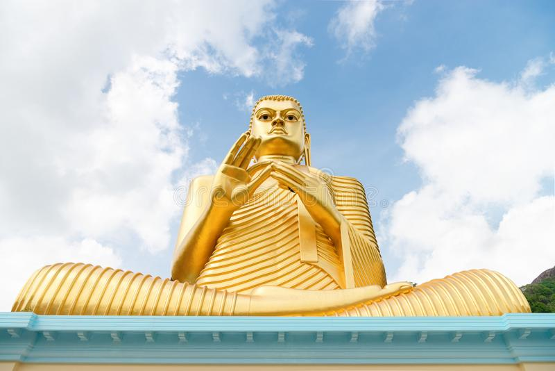 Big golden Buddha statue in wheel-turning pose. On the top of a building with blue sky on background stock images
