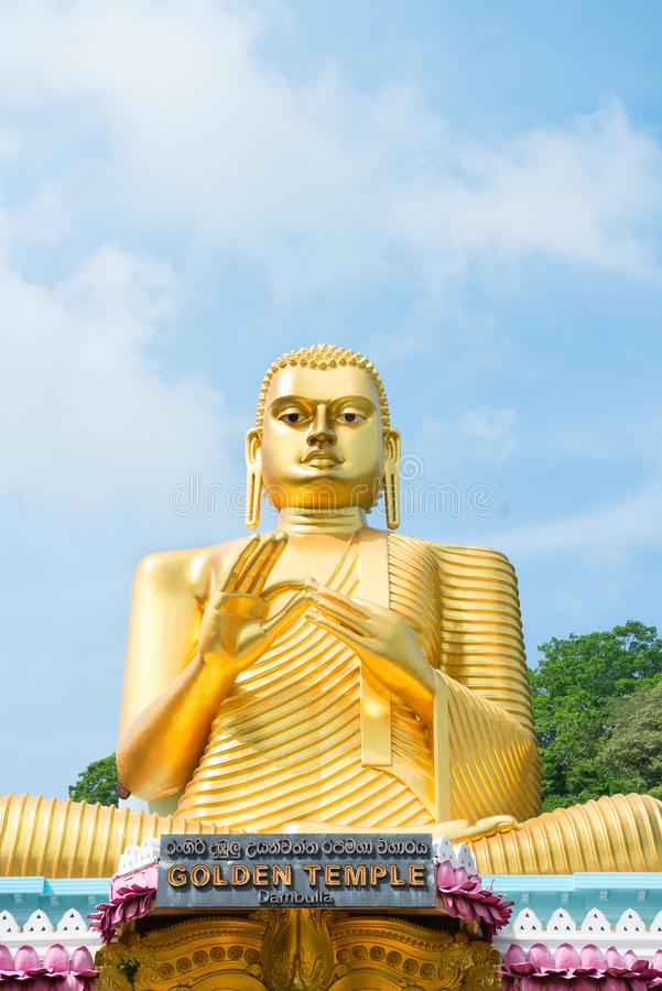 Big golden Buddha statue in wheel-turning pose in Dambulla Golden temple. Big golden Buddha statue in wheel-turning pose on the top of Golden temple in Dambulla royalty free stock photos