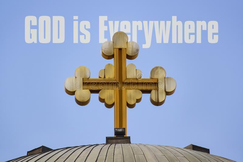 God is Everywhere. Big golden cross on the roof of a church and text God is Everywhere stock photography