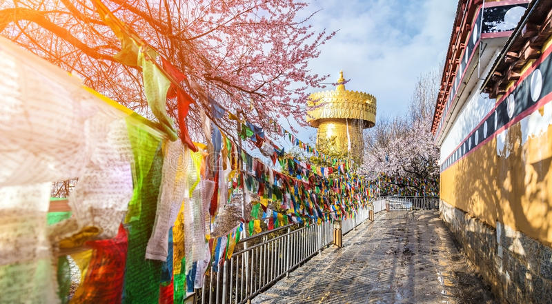Big golden prayer wheel with prayer flags and cloudy blue sky b stock images