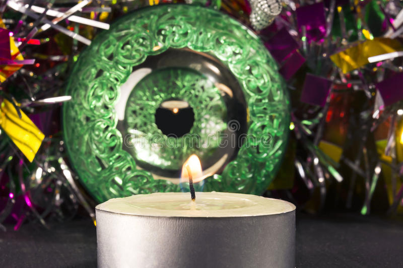 Big green carved mirror xmas ball with candle and tinsel, selective focus royalty free stock photo