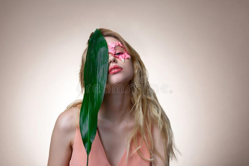 Blonde-haired model holding big green leaf near her face royalty free stock images