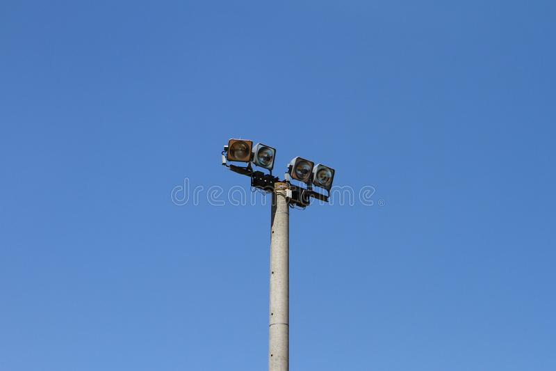 Big grey concrete lighting pole on a blue sky background, objects photo. Big concrete lighting pole on a blue sky background, objects photo royalty free stock photography