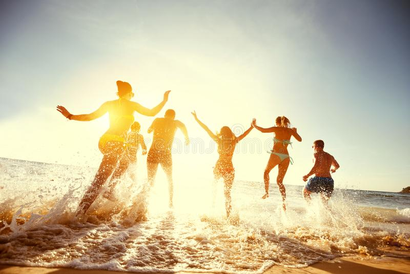 Big group friends sunset sea beach run royalty free stock images