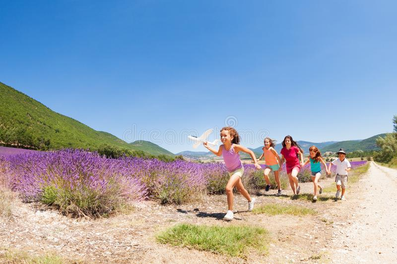 Kids having fun running with toy airplane. Big group of happy age-diverse kids running with toy airplane through lavender field in summer Provence stock photo