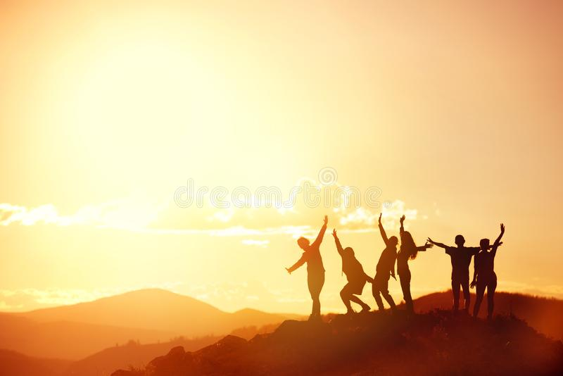Happy friends or big family`s silhouettes at sunset mountains stock image