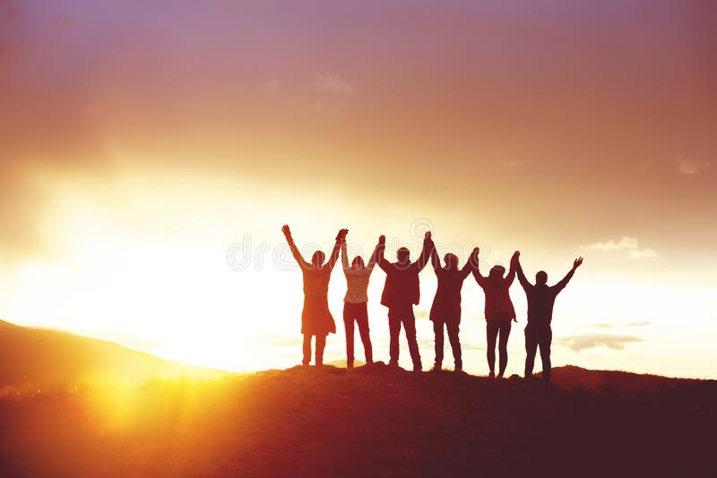 Big group happy people`s silhouettes success raised hands royalty free stock photo