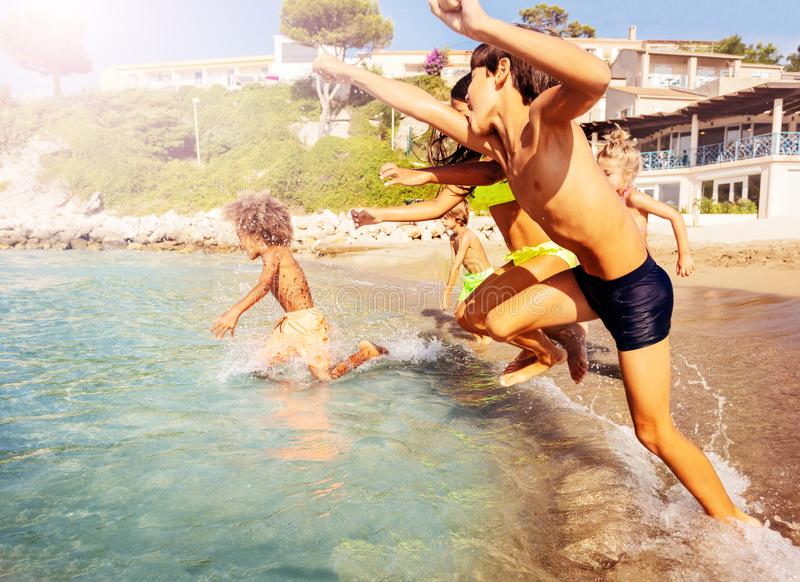Kids running into sea spending summer at seaside. Big group of multiethnic kids running into the sea, spending summertime at the seaside royalty free stock images