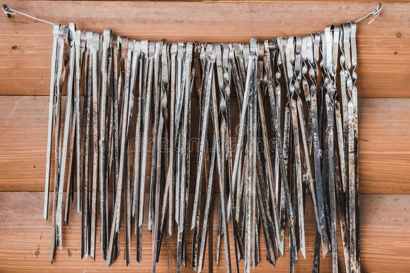 A big group of old metal skewers for meat is on a wire on two nails on an orange wooden boards wall background. A big group of old metal skewers for meat hangs stock photo