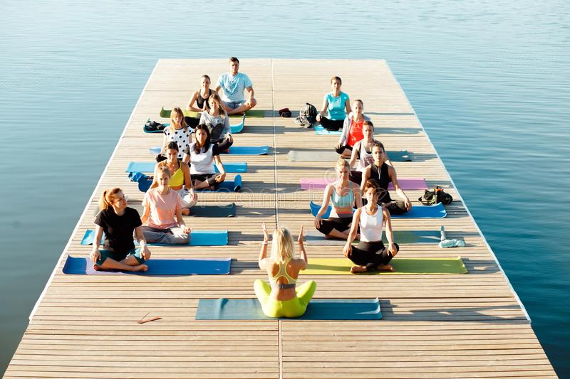 A big group of people attending yoga classes on a pontoon near the lake stock photography
