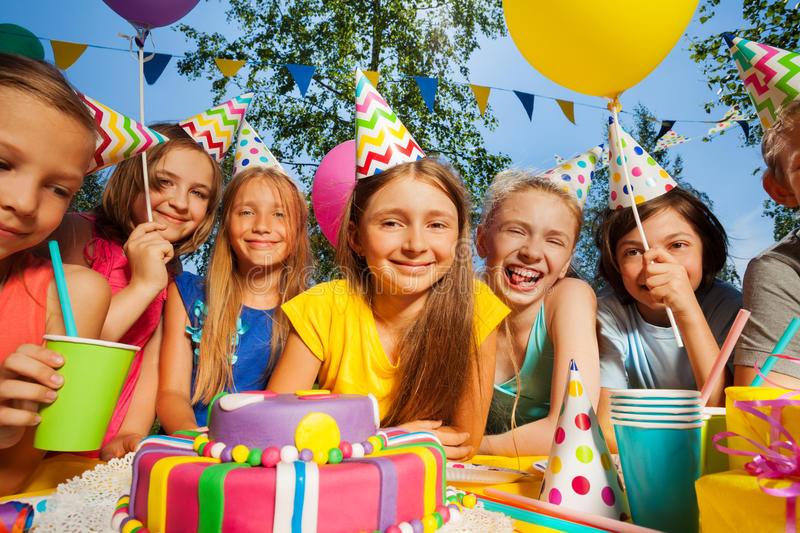Big group of smiling kids around birthday cake. Big group of smiling kids in party hats, standing in a row around the birthday cake stock photo