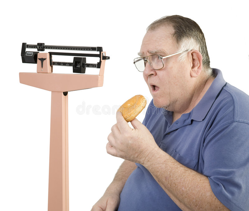 Big guy and donut looking at scale royalty free stock photo