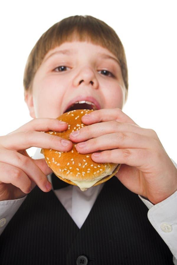 Big hamburger. Young fat school boy eating big hamburger stock photography