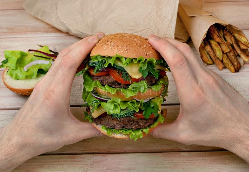 Big hamburger in the hands of a man at a wooden table stock photos