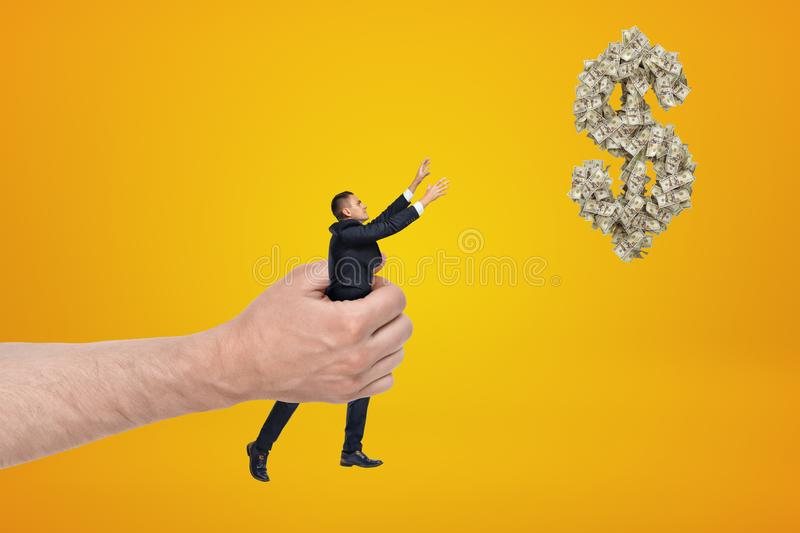 Big hand holding small businessman reaching out with his both hands for dollar symbol made up of dollar bills and royalty free stock photo
