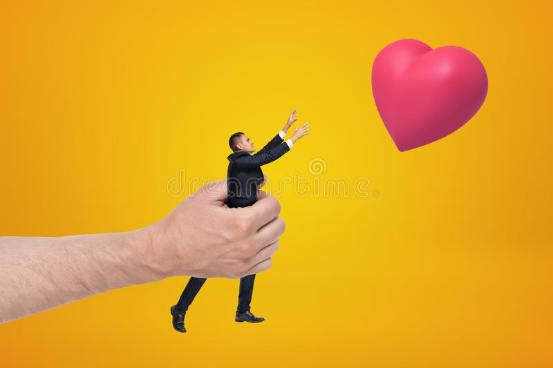 Big hand holding small businessman reaching out with his both hands for red valentine heart on amber background. royalty free stock photo
